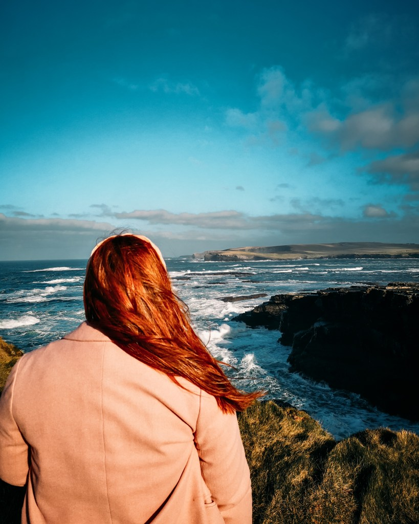 Irish woman with red hair and wearing a pink coat looking out over the Irish coastline.