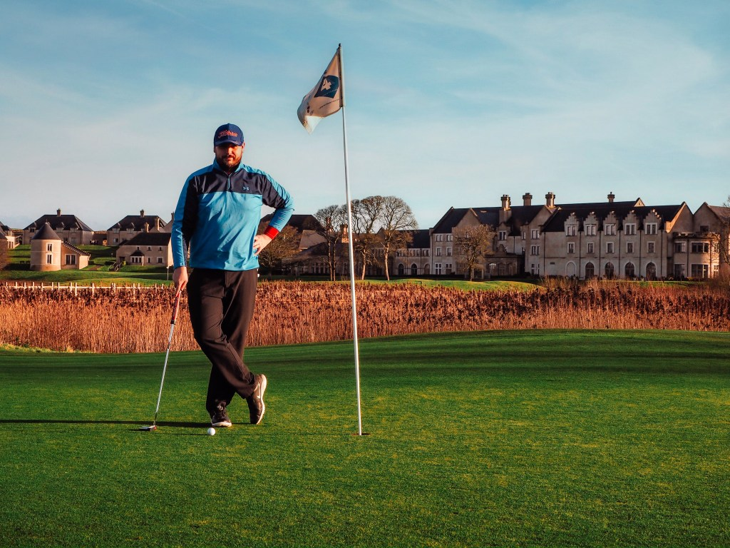 Man in blue top standing beside a golf flag after putting his golf ball