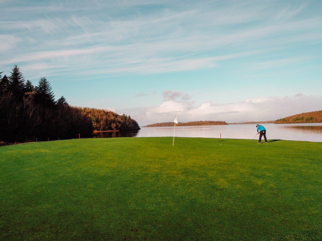 Male golfer in a blue top putting a ball on the signature hole in Lough Erne.
