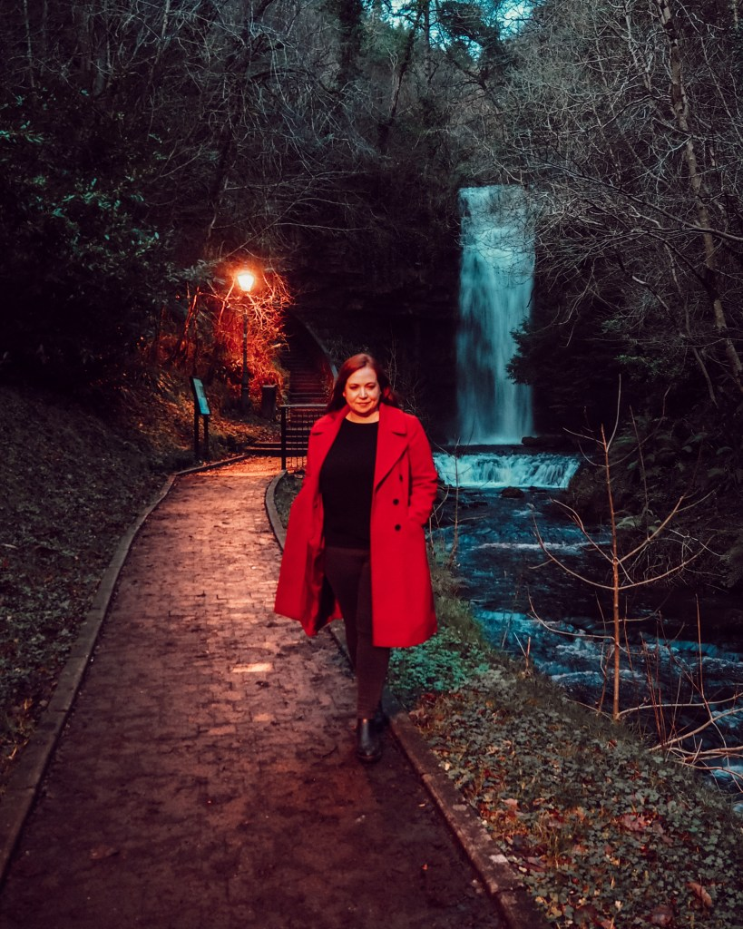 Woman in red coat standing in front of Glencar Waterfall in Leitrim Ireland