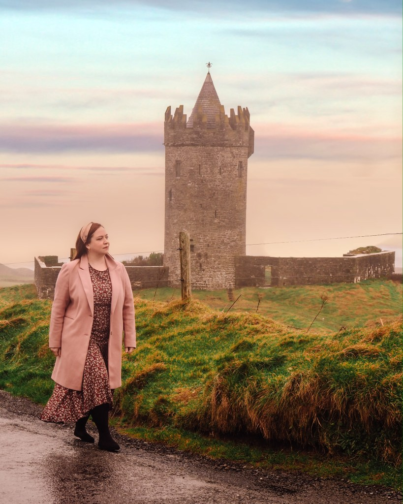 Woman wearing a floral dress and a pink coat walking past a beautiful old tower house in County Clare in Ireland.