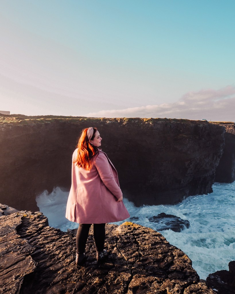 Woman in a pink coat standing at the edge of Kilkee cliffs in County Clare Ireland overlooking the crashing waves of the Atlantic Ocean
