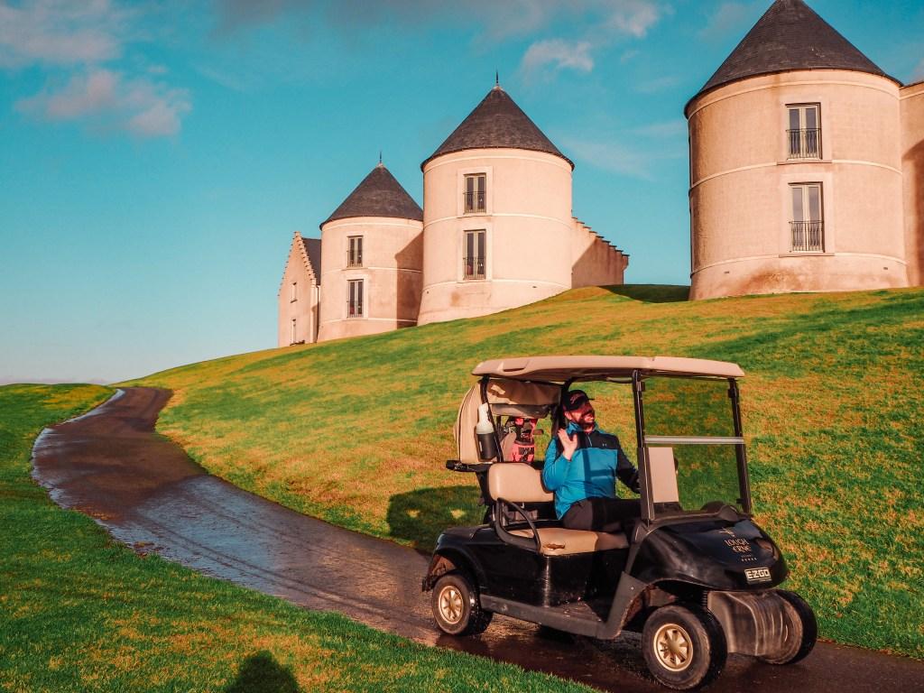 Male golfer in a blue top driving a golf cart in Lough Erne.