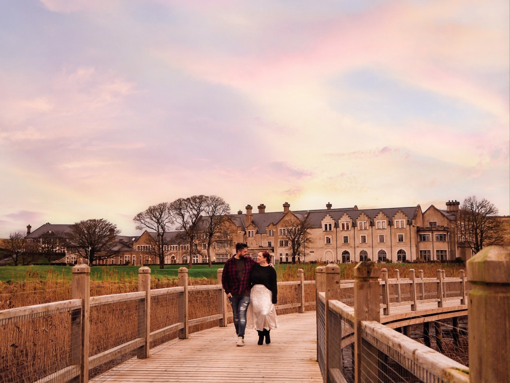 Couple walking hand in hand over a wooden bridge at Lough Erne resort one of Ireland's most romantic hotels under a beautiful sunset.