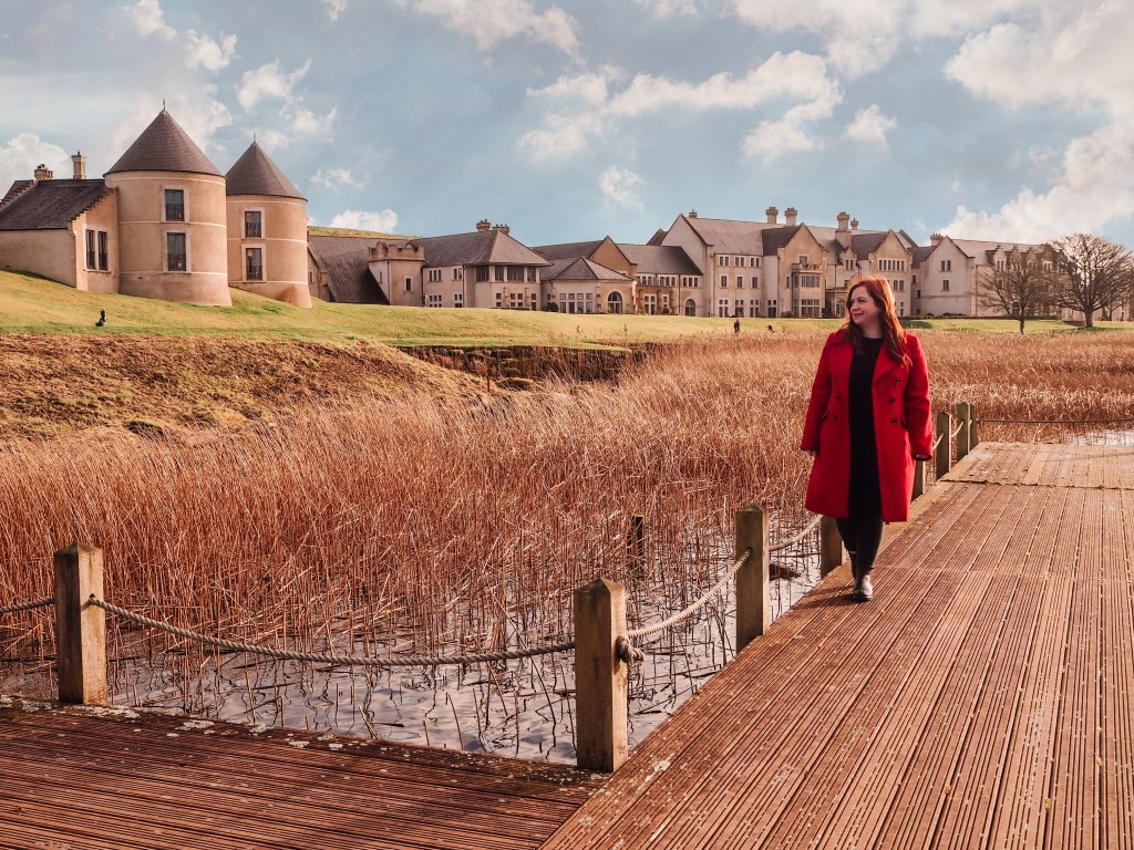 Travel blogger All about RosaLilla walking beside the lakeshore on a wooden jetty wearing a red coat. Hotel building can be seen in the background.
