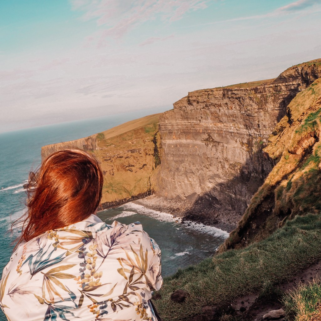 Woman looking over the cliff edge at the Cliffs of Moher Ireland
