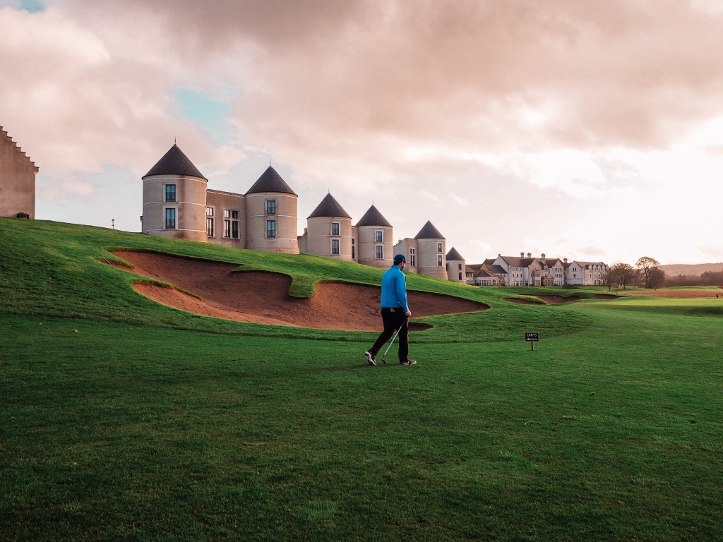 Man in a blue top walking The Nick Faldo golf course at Lough Erne
