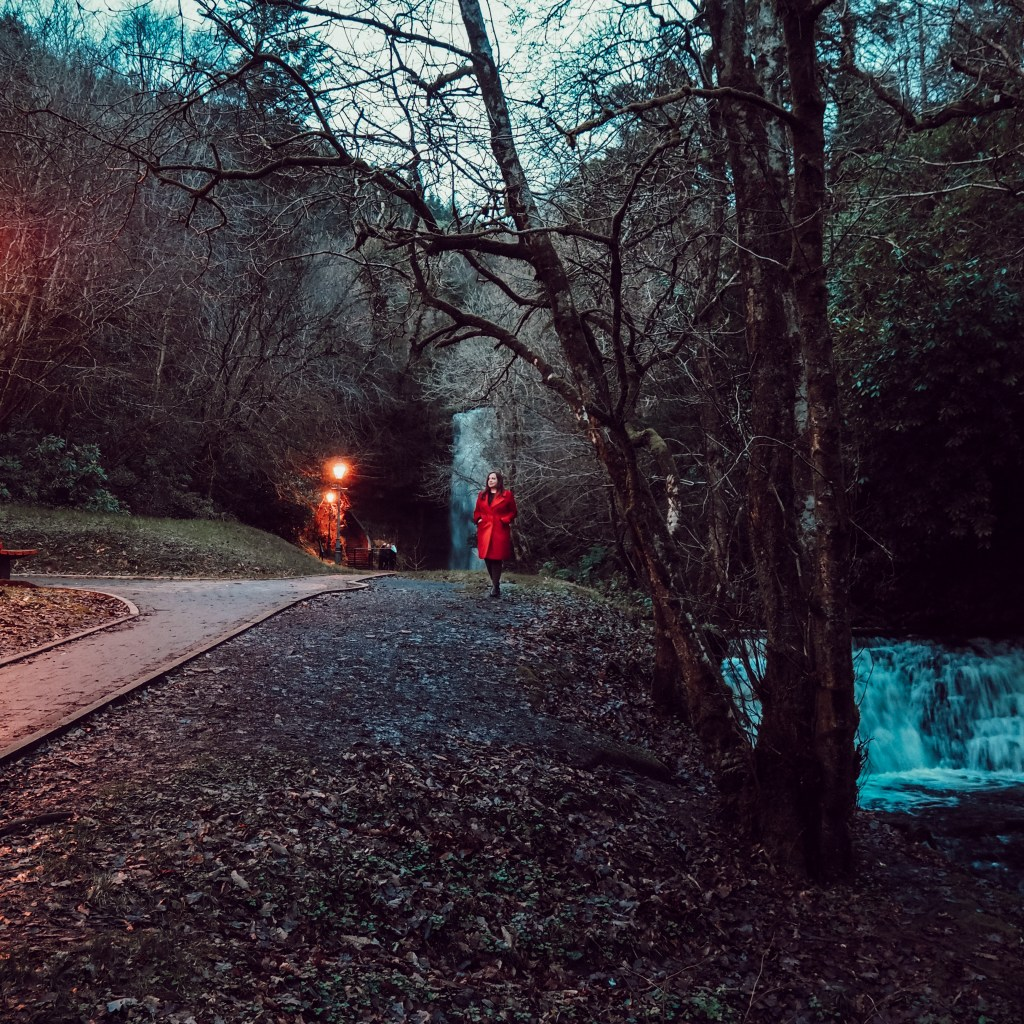 Woman in red coat standing in front of Glencar waterfall in Leitrim Ireland.