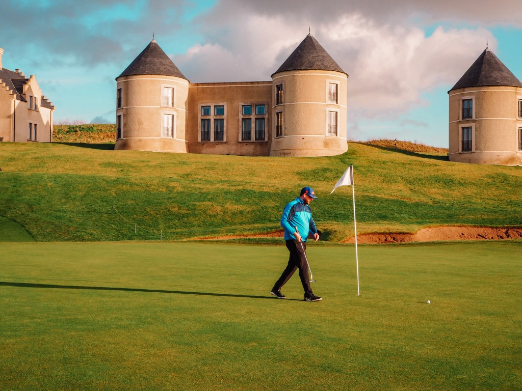 Male golfer in blue top and black trousers walking towards a golf flag.