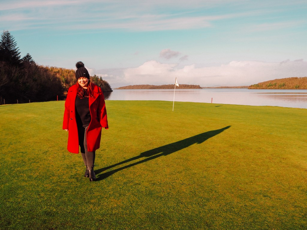 Woman in red coat walking on a golf course in Northern Ireland with a golf flag in the background.