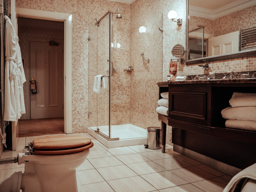 Bathroom with dark wooden counters and beige mosaic tiles at the Dovecote suite in Lough Erne Resort