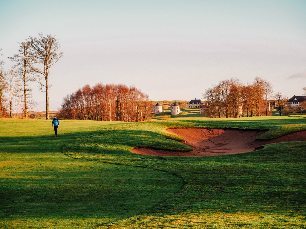 Male golfer in a blue top walking with a golf club near a sand bunker on a golf course in Ireland.