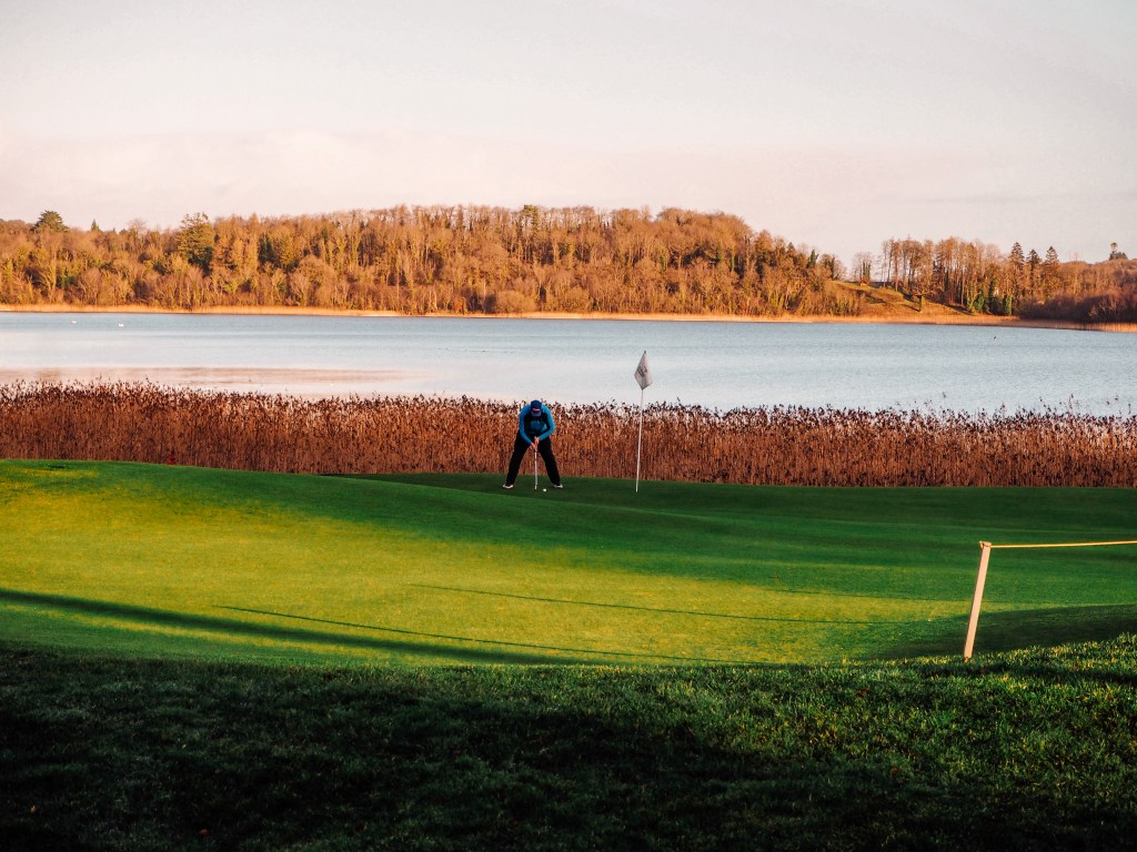 Male Golfer in blue top putting a ball on the first hole of Lough Erne Golf Resort.