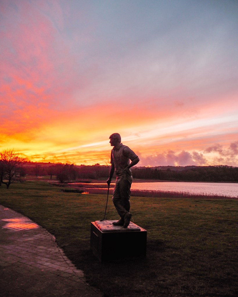 Statue of Nick Faldo at Lough Erne Golf Resort silhouetted against a magical sunset