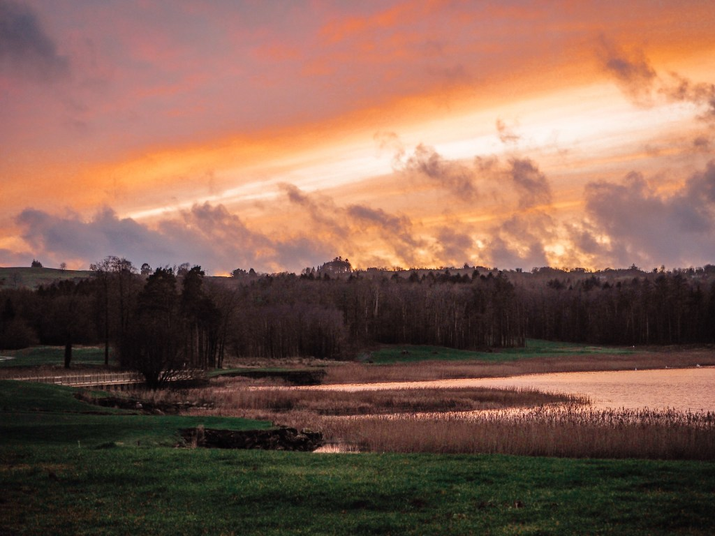 Beautiful pink and gold sunset over Castle Hume Lough in Northern Ireland