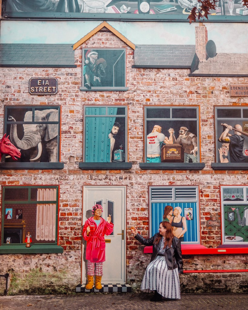 Woman raising a glass of wine to a mural of a woman in Belfast's Cathedral Quarter. Best Instagram Spots Belfast