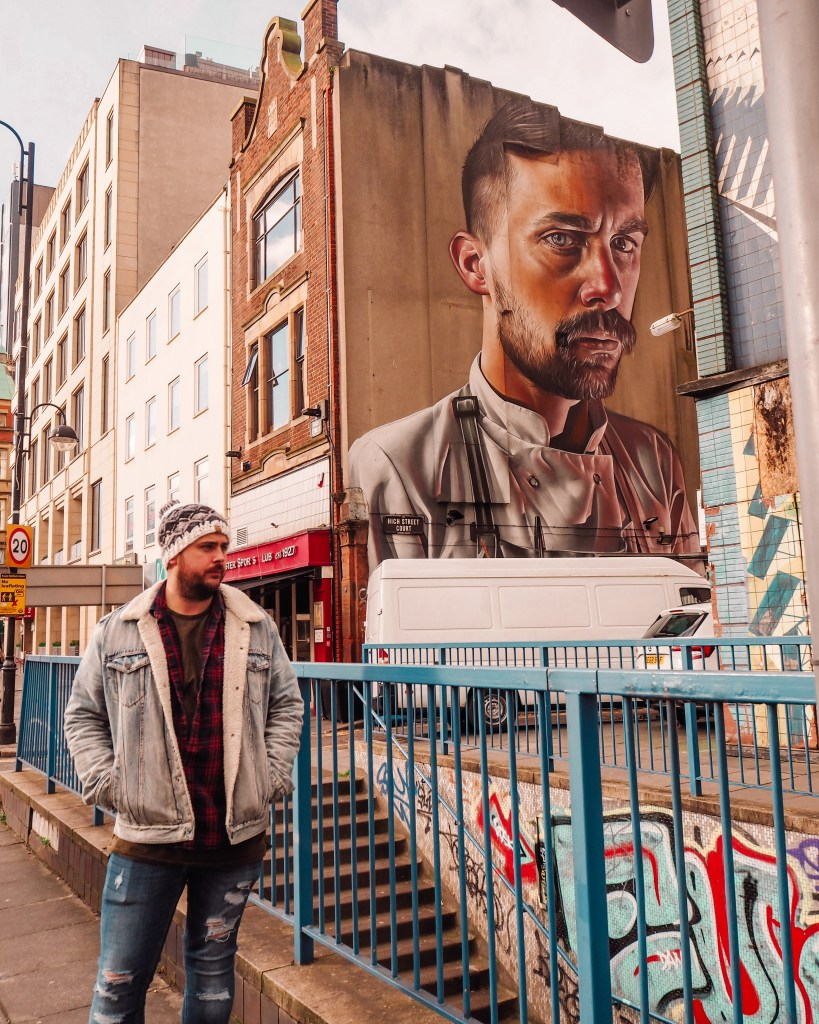 Man in a fleece lined denim jacket standing in front of The Chef by Smug One street art in Belfast city
