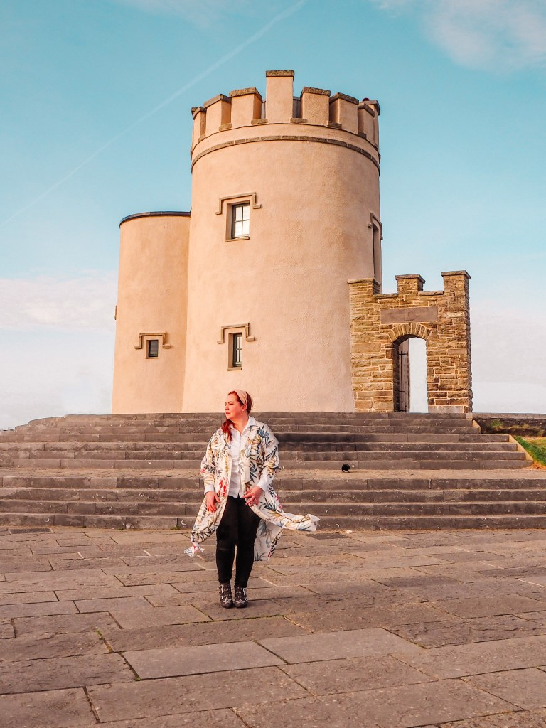 Woman in a long coat standing in front of O'Brien's Tower at the Cliffs of Moher