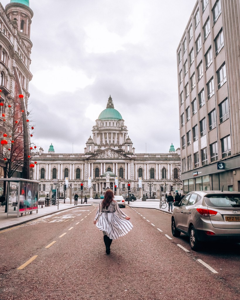 Woman wearing a white dress as she flicks her skirt in front of Belfast City Hall