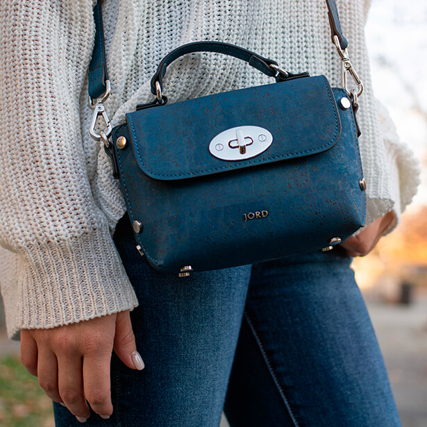 Woman wearing a peacock blue and gold vegan leather handbag designed by JORD
