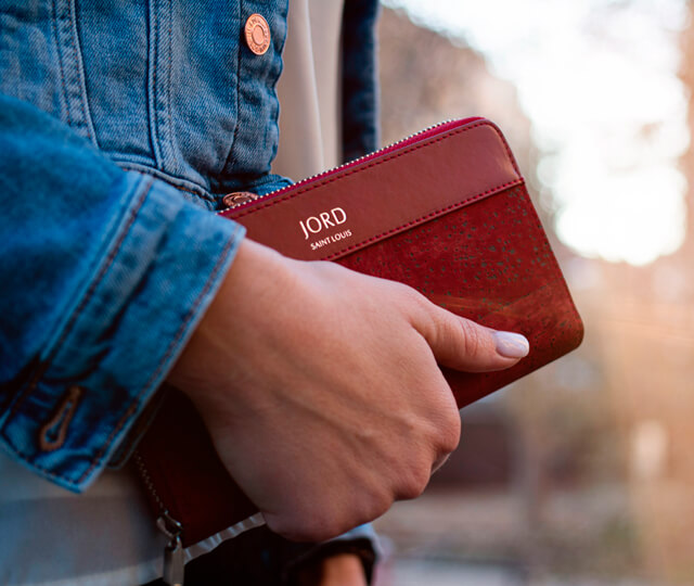 Woman wearing a denim jacket holding a red vegan leather wallet