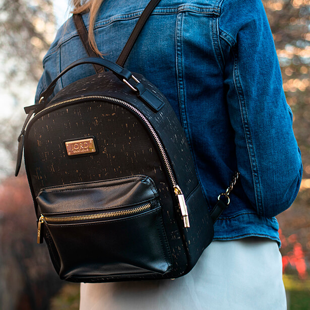 Woman in a denim jacket wearing a black jord vegan leather backpack