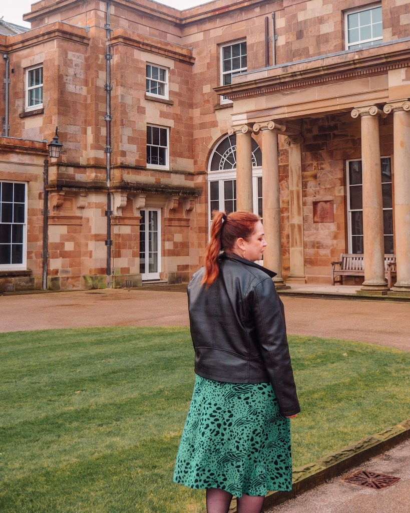 Woman in a green dress and black leather jacket walking the gardens of Hillsborough Castle and gardens in nortern ireland.