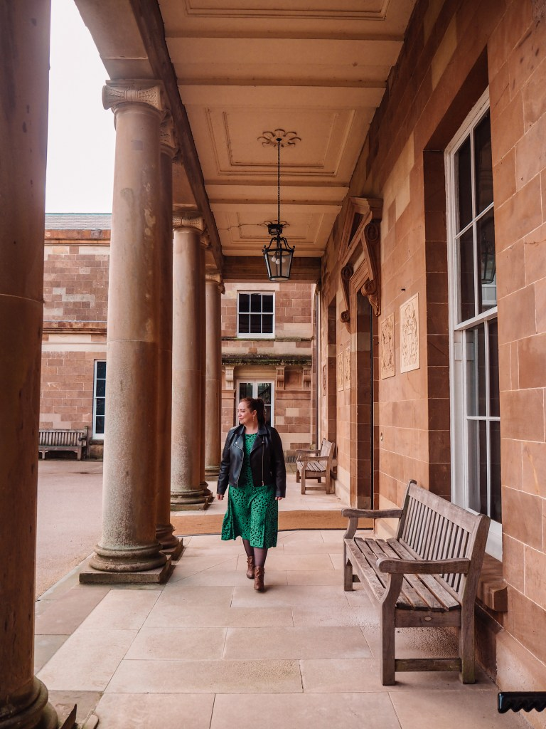 Woman in a green dress walking under the arches of Hillsborough Castle Northern Ireland