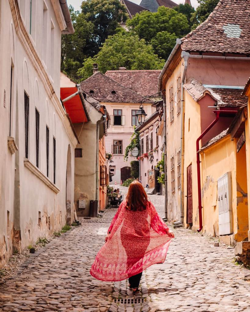 Woman with a long red flowy kimono walking along the cobbled streets of Sighisoara Romania