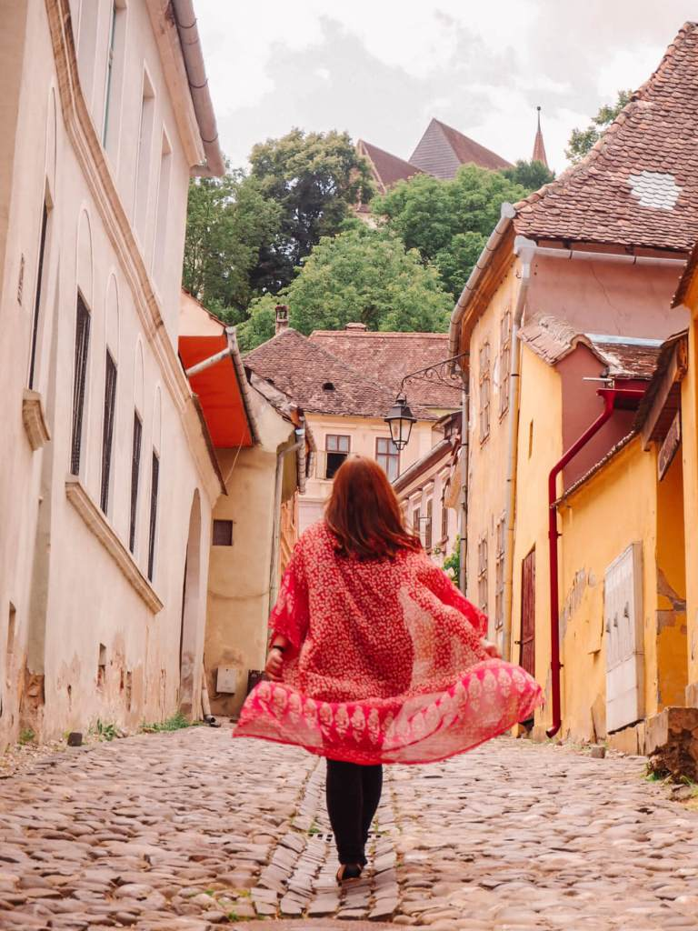 Woman walking through the colourful streets of Sighisoara