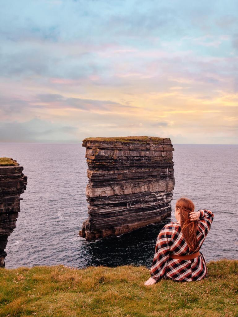 Woman sitting on a cliff edge at Downpatrick Head on the Wild Atlantic Way Ireland