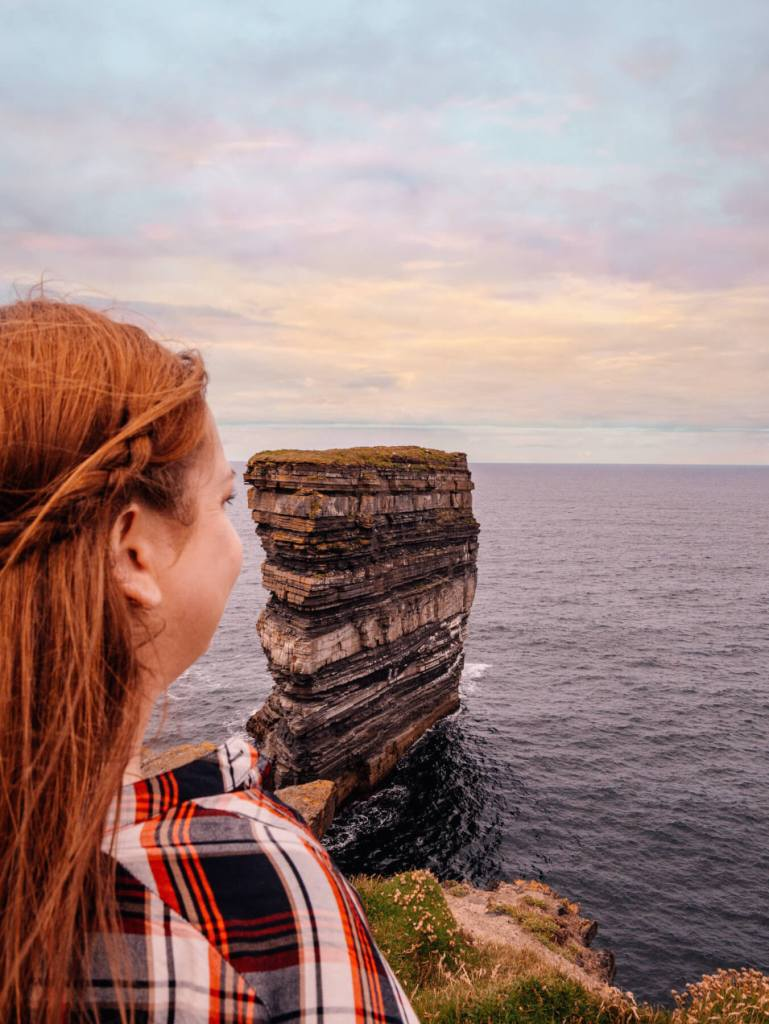 Woman looking out at Dun Briste sea stack at Downpatrick Head in county Mayo