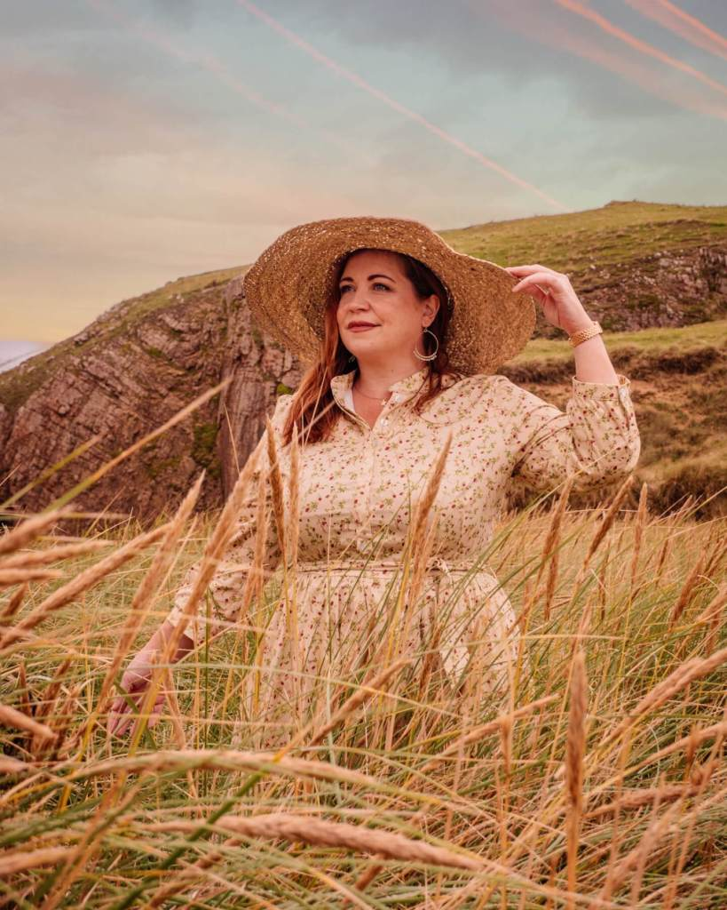 Woman in a yellow floral dress and straw hat enjoying her staycation in Ireland
