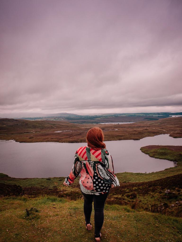 Woman wearing a colourful yop overlooking the mountain views at Lough Salt in County Donegal Ireland. Staycation Ireland Ideas