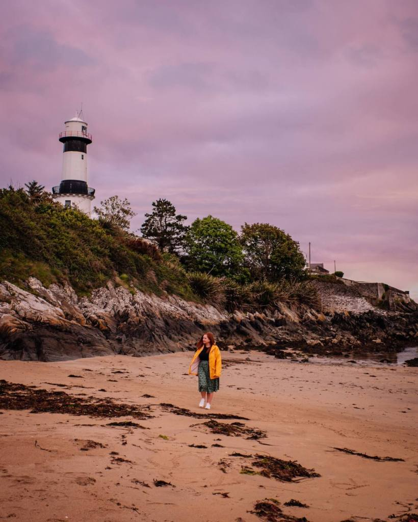 Women wearing a yellow raincoat walking around the base of Stroove lighthouse at Inishowen peninsula in County Donegal Ireland