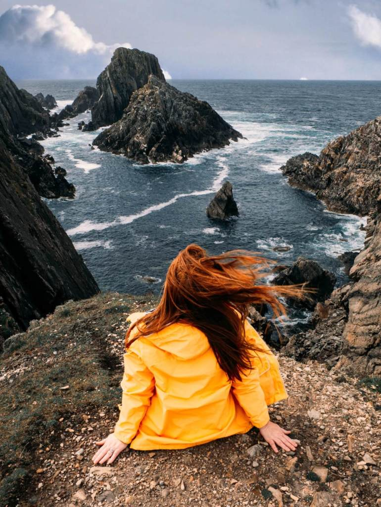 Woman wearing a yellow raincoat sitting at the cliff edge at Malin Head in County Donegal Ireland