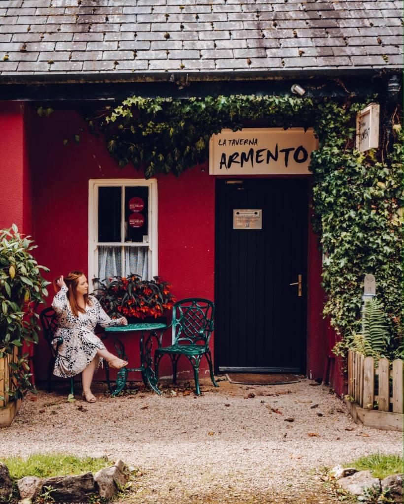 Woman sitting outside La Taverna Armento Italian restaurant at Brooklodge