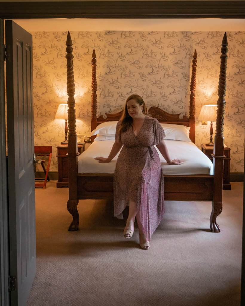 Woman sitting on the bed of a country style four poster bed at Brooklodge Hotel and Macreddin Village