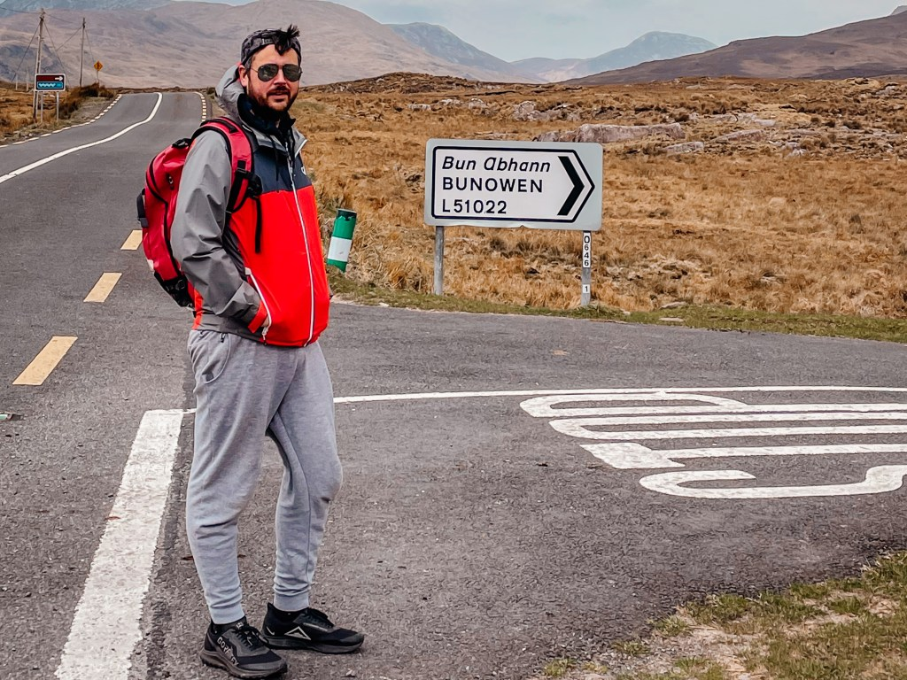 Man wearing a grey tracksuit and red rain jacket at the start of the Killary Harbour Coastal Walk in Connemara Ireland