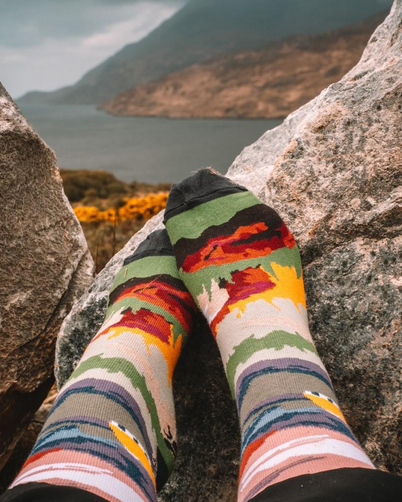 Feet wearing Connemara socks with the backdrop of Killary fjord