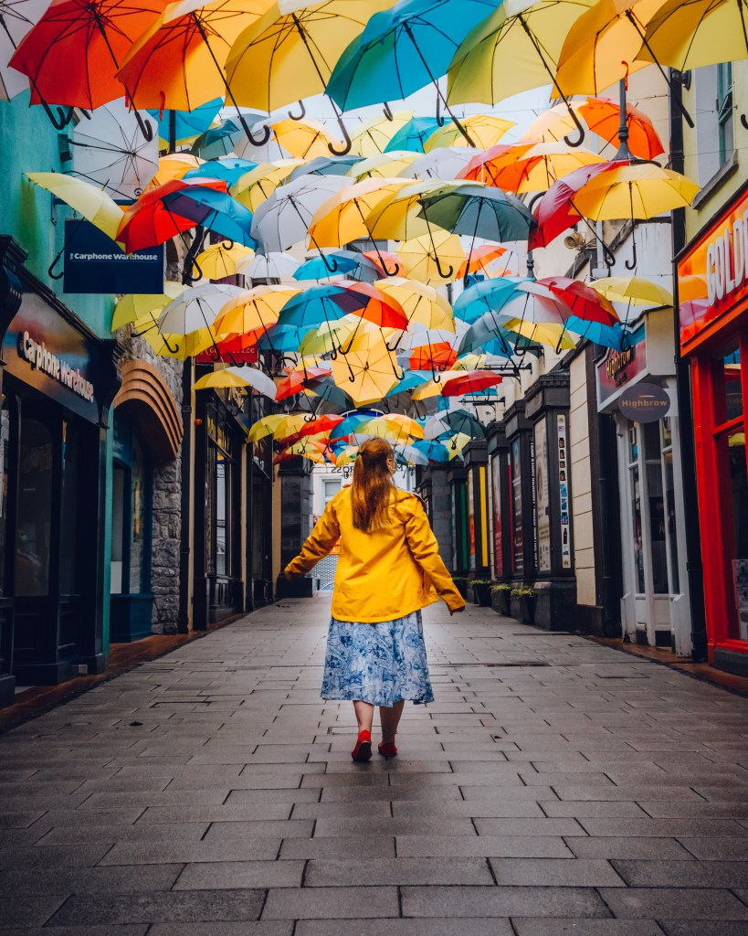 Woman in a yellow raincoat walking under an umbrella sky in the medieval city of Kilkenny