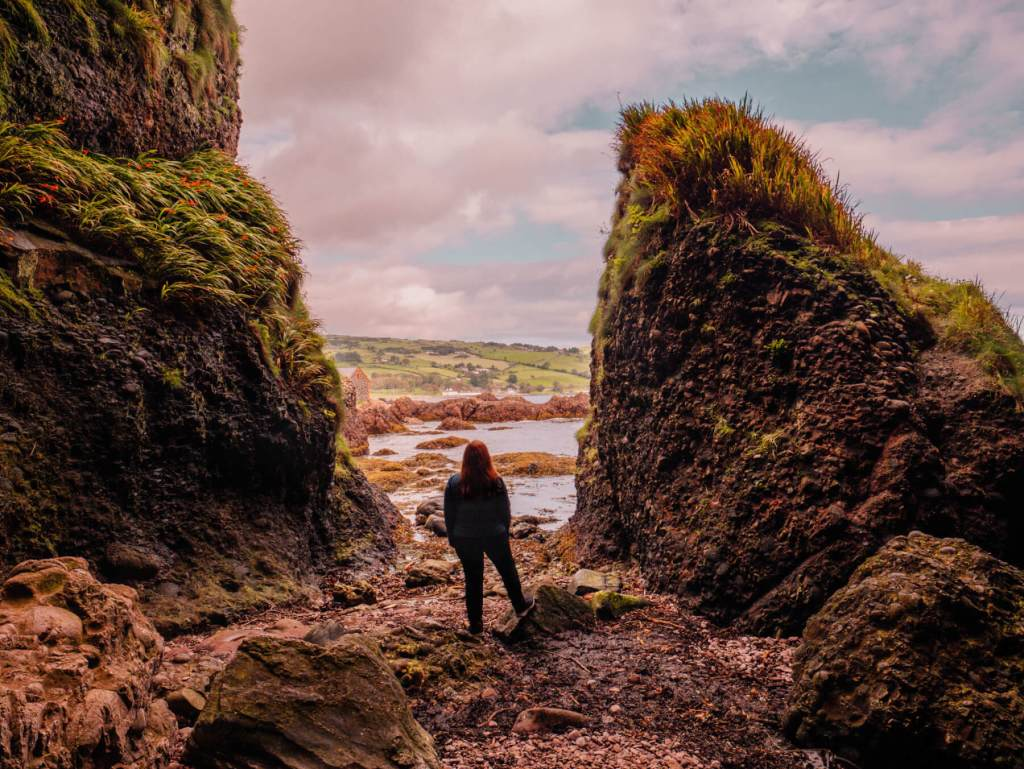 Woman looking at the Antrim coastline at Cushendun caves a games of thrones filming location in Northern Ireland