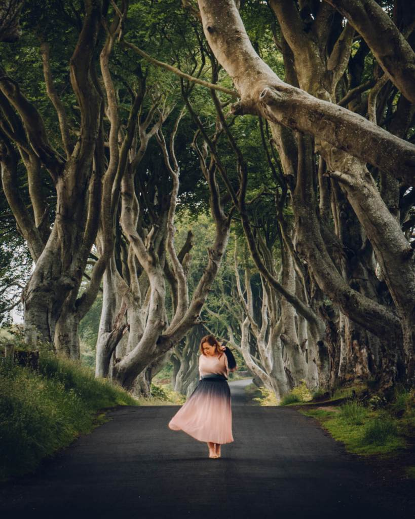 Woman in a pink dress at The Dark Hedges in Antrium the ultimate Game of Thrones filming location