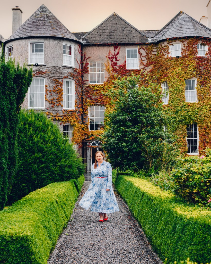 Woman in a blue dress walking around the gardens of Butler House Kilkenny