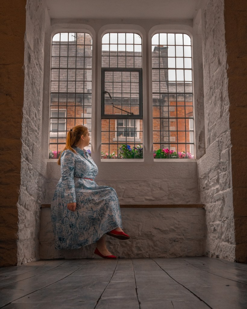Woman in a blue dress sitting on a window sill at Rothe House and gardens in Kilkenny Ireland
