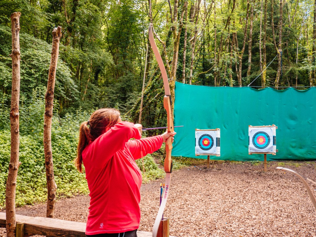 Woman in a red top holding an archery bow at Castlecomer Discovery Park Kilkenny