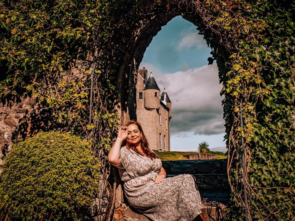 Woman soaking up the sun in a garden archway at Ballygally Castle Hotel in County Antrim Northern Ireland