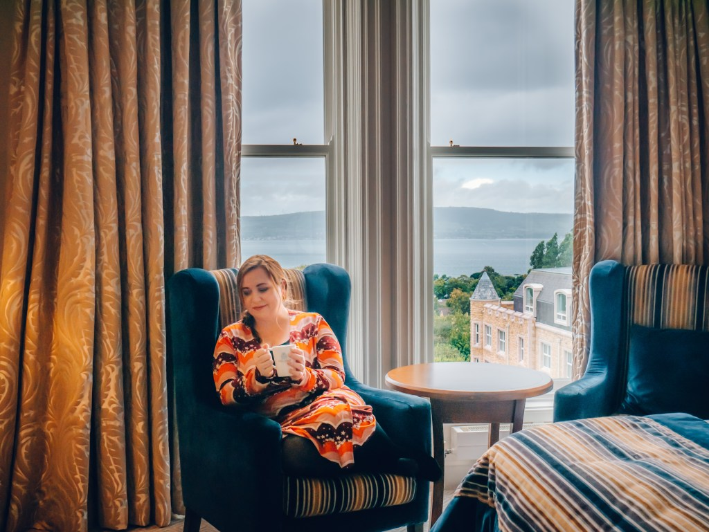 Woman drinking tea in a chair in her hotel bedroom at Culloden Estate
