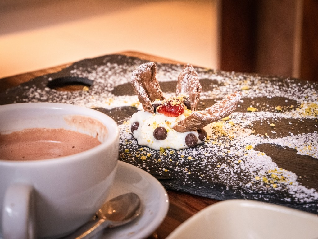 Cup of hot chocolate beside a plate of cannoli