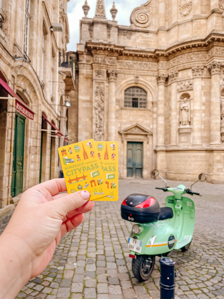 Woman holding up two Bordeaux city passes perect for your Bordeaux itinerary when you are exploring Bordeaux